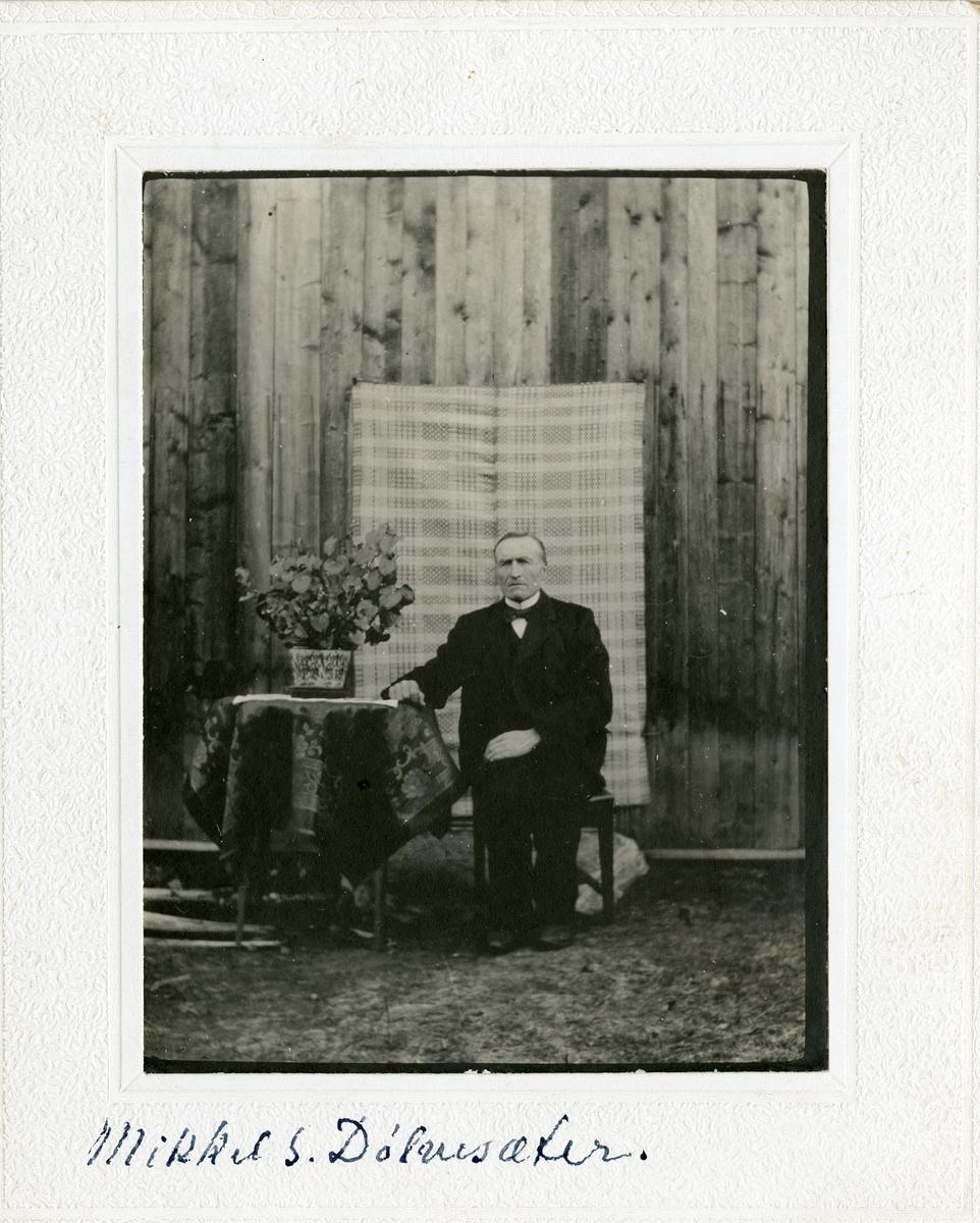 Mikkel S. Dølvensæter sittende ved et bord foran et kristenteppe.