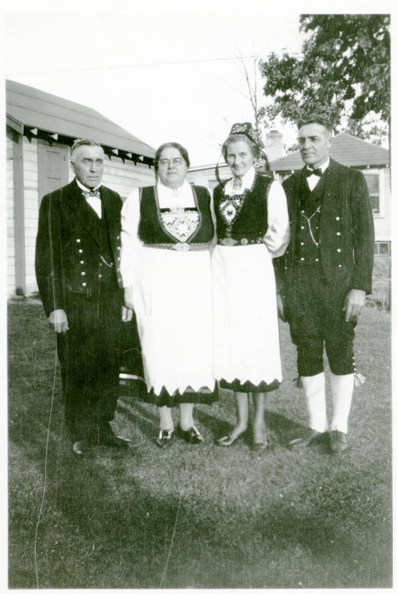 To kvinner og to menn oppstilt utenfor et hus i Amerika. Alle er kledd i bunad.