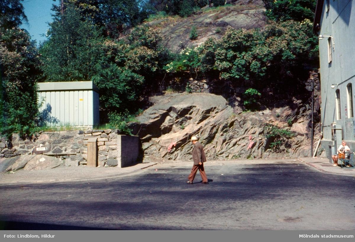 En man går förbi busshållplats vid Gamla Torget i Mölndal, 1970-tal. Till höger ses gaveln på huset Kvarnbygatan 41, tidigare brandstation och garage för polisbilar, numera Mölndals målarskola.  För mer information om bilden se under tilläggsinformation.