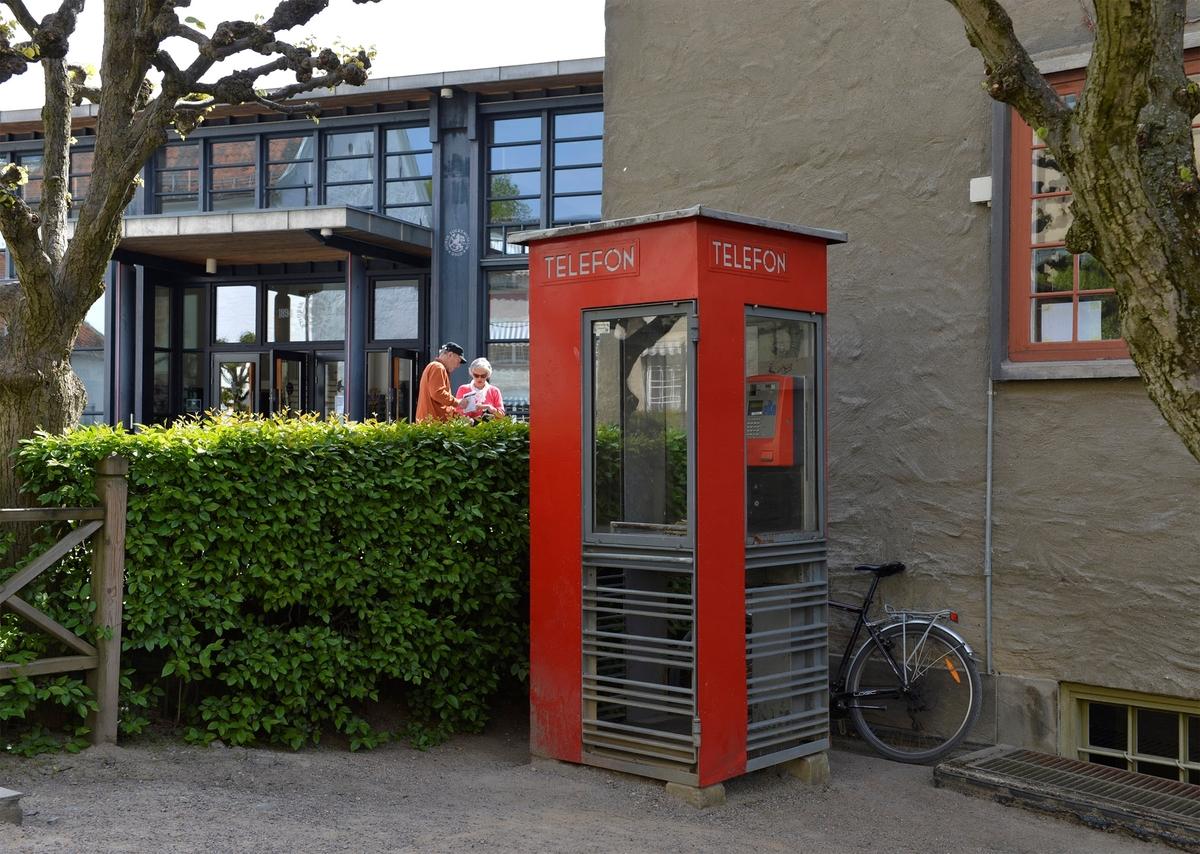 Denne telefonkiosken står rett innenfor inngangen til Norsk Folkemuseum på Bygdøy, og er en av 100 verna telefonkiosker rundt om i Norge.  De røde telefonkioskene ble laget av hovedverkstedet til Telenor (Telegrafverket, Televerket) Målene er så å si uforandret.  Vi har dessverre ikke hatt kapasitet til å gjøre grundige mål av hver enkelt kiosk som er vernet.  Blant annet er vekten og høyden på døra endret fra tegningene til hovedverkstedet fra 1933. Målene fra 1933 var: Høyde 2500 mm + sokkel på ca 70 mm Grunnflate 1000x1000 mm. Vekt 850 kg. Mange av oss har minner knyttet til den lille røde bygningen. Historien om telefonkiosken er på mange måter historien om oss.  Derfor ble 100 av de røde telefonkioskene rundt om i landet vernet i 1997. Dette er en av dem.