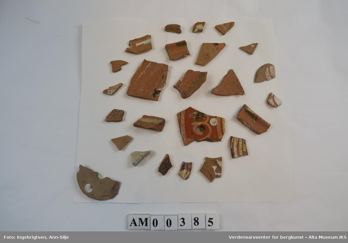 Et ark med mange keramikkfragmenter i ulike størrelser. Noen av fragmentene har rester etter glasur.   Keramikkfragmentene varierer i størrelser fra 1,5 cm til 5,5 cm i lengde.