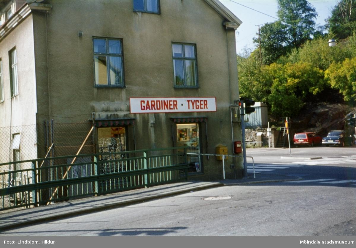 En tyg- och gardinaffär i huset Kvarnbygatan 4 vid Gamla Torget i Mölndal. Fotografiet är taget efter försäljningen av Rasmussons skoaffär vid slutet av 1970-talet. Vy från Forsebron.  För mer information om bilden se under tilläggsinformation.