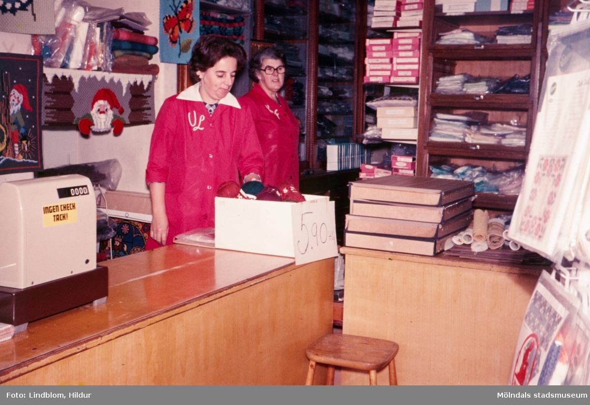 Två kvinnor fotograferade vid kassan i Kvarnbyns garn och handarbetsaffär med adress Kvarnbygatan 37 i Mölndal, 1970-tal. Till vänster ses Ulla, som senare kom att arbeta i Rasmussons skoaffär och till höger Kajsa som var ägare av garnaffären.  För mer information om bilden se under tilläggsinformation.