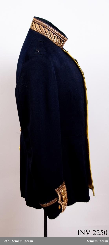 """Stl B 152. Mörkblått kläde, avskuren i midjan, skört med fickor bak och broderad krage, klaffar och runt uppslagen. Enkelknäppt med åtta knappar av m/större generalitet och generalstab. Gul passpoal utmed framkanterna och ficklocken i  skörtet. Ett flertal svarta silkestränsar på framstyckets vänstra sida, för fastsättande av spännen, ordnar och medaljer.  På vardera av de bakre fasonerade ficklocken tre knappar av m/1767 större, gjord hos Sporrong. Gult sidenfoder med vänster knappinfodring i kläde. På axlarna slejfer av plaggets tyg och färg, för epåletter. En knapp för ägiljett. På innersidans  framstycken två tampar som ihophäktas mitt fram, sydda dubbelt  av fodertyget. Syftet är att hålla in magen, samtidigt som  plagget hålls på plats och sitter bättre. I bröstfickan vit etikett """"Militär Ekiperings AB. Kungl. Hofleverantör. Stockholm 5/10 1923. General O.G. Thörnell""""."""