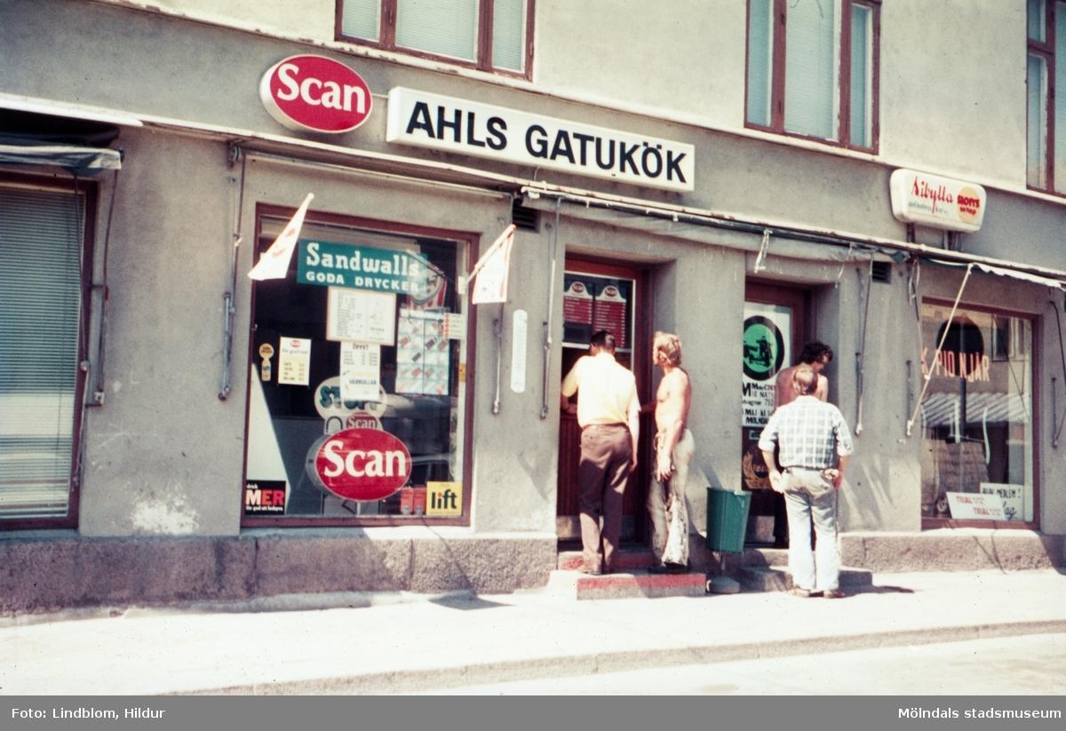 Fyra män står utanför dörren till Ahls Gatukök vid Gamla Torget i Mölndal med adress Kvarnbygatan 43, 1970-tal.  För mer information om bilden se under tilläggsinformation.