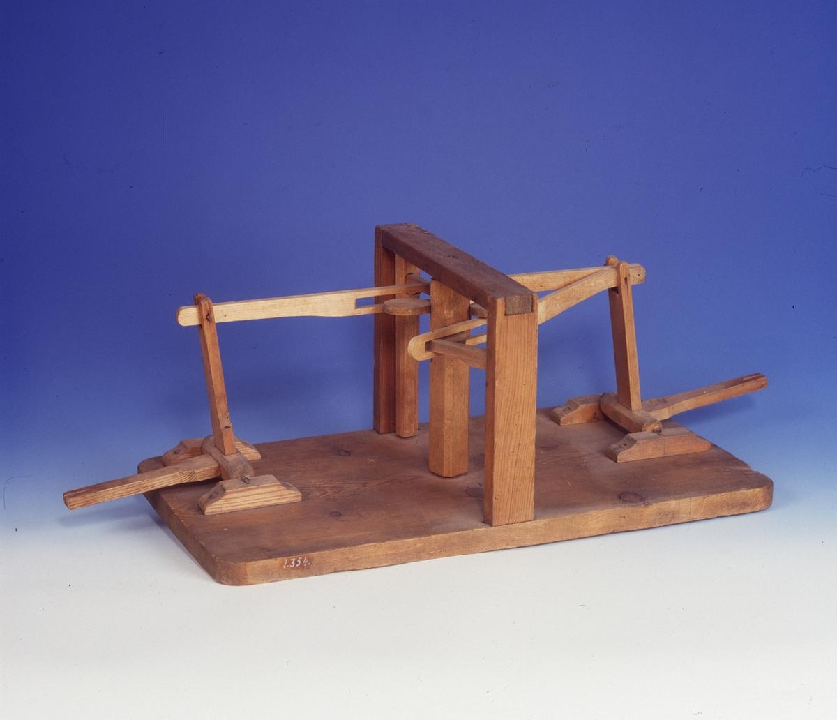 Modell ur Polhems mekaniska alfabet. Text på föremålet: LXXXII. När den kamförsedda lodräta axeln roterar, utför de båda yttre armarna en vickade rörelse.