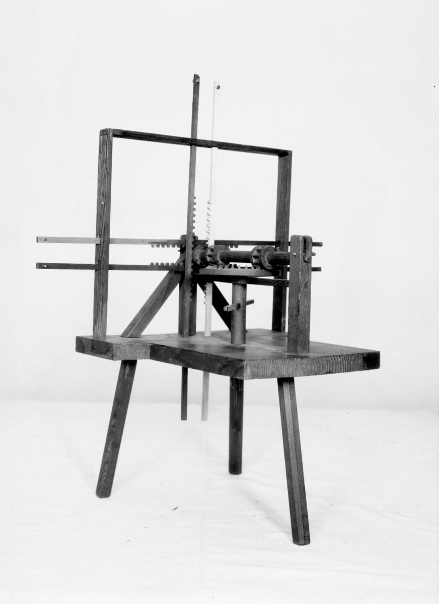 Modell ur Polhems mekaniska alfabet. Text på föremålet: LXXXIV. En roterande rörelse hos den lodräta axeln överförs till en fram- och återgående rörelse hos kuggstängerna.
