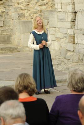 Lyshåret, ung jente iført hvit, langermet linkjole under og en blågrønn overkjole i ull står og synger for publikum i vernebygget over domkirkeruinen.