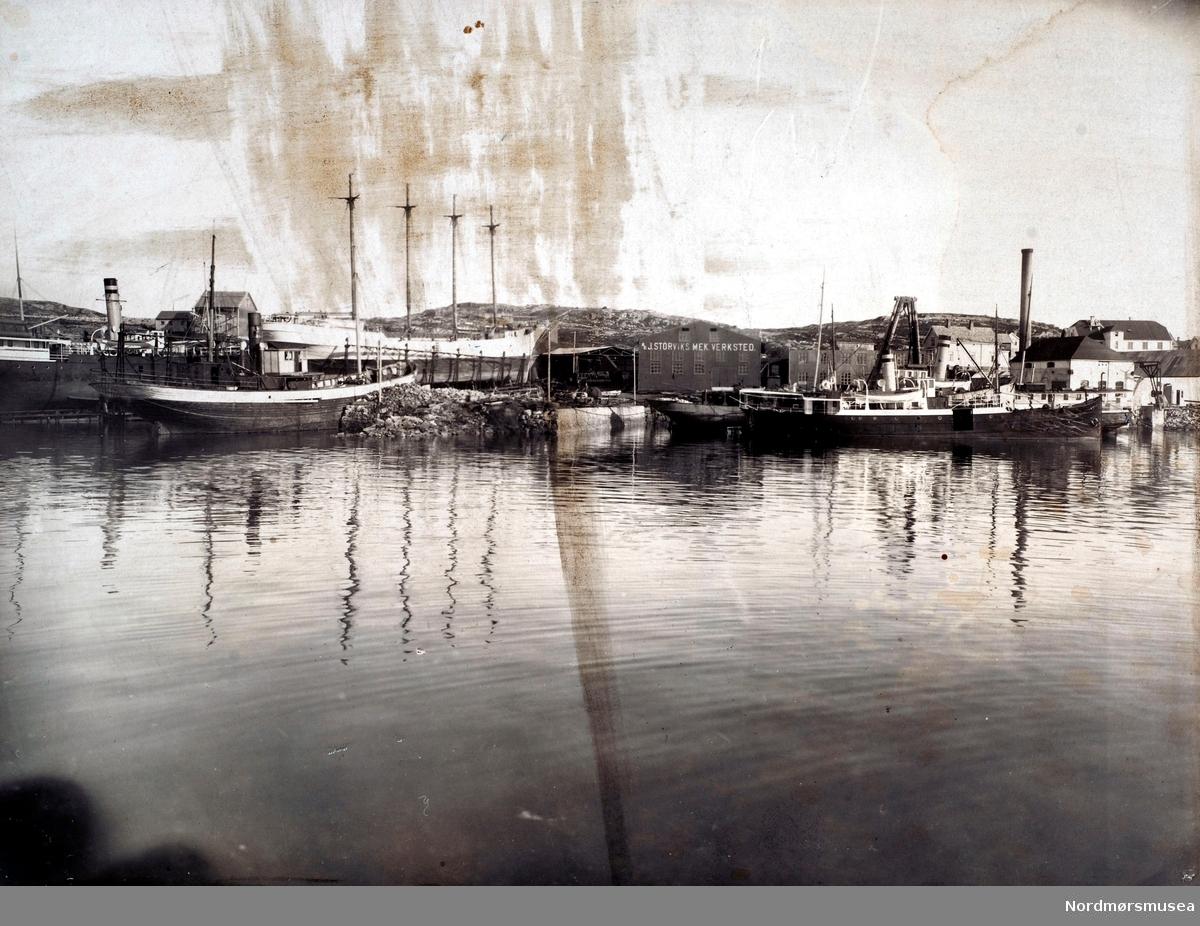 """Bilde av J. Storviks Mek. Verksted på Dahle ved Kristiansund, sett fra sjøen. Det er rekke båter ved kaier og på patentslippen. Ved kjelkrankaia ses den første kjelkrana bygd av massivt tømmer i ca. 1903 og det ligger 2 rutedampskip, ytterst D/S""""Kværnes (1)"""" tilhørende Kværnes og Grip Dampskibsselskab og innenfor ligger D/S""""Hankø"""" og det ligger en fiskekutter innerst, som vi ser hekken på til venstre for de 2 rutebåtene foran kjelkrankaia. Dette er sansynligvis verkstedets fiskekutter som ble til D/S""""Villa"""" bnr.10 til Fyrvesenet som ligger til utrustning.  På den nye patentslippvogna klinkbygd i stål 1918, den største slippen mellom Bergen og Trondheim, står 2 båter, forrest et 4-mastret seilskip, et stort finsk skonnertskip S/S""""Regina"""" som er til reparasjon etter grunnstøting og bakerst damprutebåten D/S""""Smølen""""  til Møre Fylkes Ruteselskap (MFR). Over """"Smølen"""" ses demningen på Nydammen (Storvikdammen). Foran baugen på """"Regina"""" ses blikktaket over maskinparken, lokke-og klippemaskin, platevals, spantbukkemaskin, ved innkjørselen til verkstedet. På nordsiden av piren foran bakerste båt på patentslippen ses damperen D/S""""Bjugna"""", tilhørende Julius Loennechen med flere, som får innsatt maskin og overbygg. Piren er bare delvis utfyllt og bygd. Over bakerste båt på patentslippen ses bolighuset til verkstedet med uthus, bygd ca. 1910 og brant på 1980-tallet, hvor familien Hjelmaas bodde, senere familien Paul Storvik.  Bolighuset var et gammelt meieri i tømmer flyttet fra Straumsnesset og bygd opp ca. 1910 og brant på 1980-tallet. Til høyre for Regina ses maskinverkstedbygningen med firmanavnet på veggen, bygget etter brannen i februar/mars 1911 og revet etter 1980. Over høyre del av taket på maskinverkstedbygningen ses mønet på bolighuset til John Olsen Storvik, senere barna hans og revet etter 1980.  Til høyre for maskinverkstedsbygningen ses først sjauer og malerbygget deretter lagerutleveringsbygget, med kontorer for timeskriver og verksmester i 1. etasje, og foran lag"""