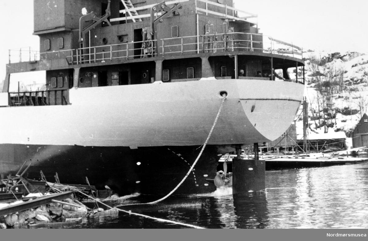 """Bildet viser Sterkoder Mek. Verksted på Nordlandet i Kristiansund. Lastebåten er på vei ut i sjøen, ved stabelavløpingen fra den gamle beddingen. Dette er en av lastebåtene som ble levert til rederiet P/T Pann, (NWE) Indonesia (den Indonesiske stat). Sansynligvis den første av lastebåtene Sterkoder Mek Verksted bygde for denne oppdragsgiver og gitt bnr. 72 med navnet M/S """"Inaran"""" på 1599 bruttoregistertonn levert i 1977.                       Sterkoder bygde 4 skip totalt til denne oppdragsgiver :                                                        Slepebåten M/S """" Selat Tanakeke"""" bnr. 75 på 1166 BRT levert i 1977.                                    Slepebåten M/S """" Selat Glasa"""" bnr. 76 på 1166 BRT levert i 1977.                                           Lastebåten M/S """" Isabela"""" bnr. 73 på 650 BRT levert i 1977.                                                 Lastebåten M/S """" Iweri"""" bnr. 74 på 650 BRT levert i 1978. Info: Peter Storvik. -- Ukjent fotograf. Bildet kan være fra 1983. Serie. Fra Nordmøre Museums fotosamlinger."""