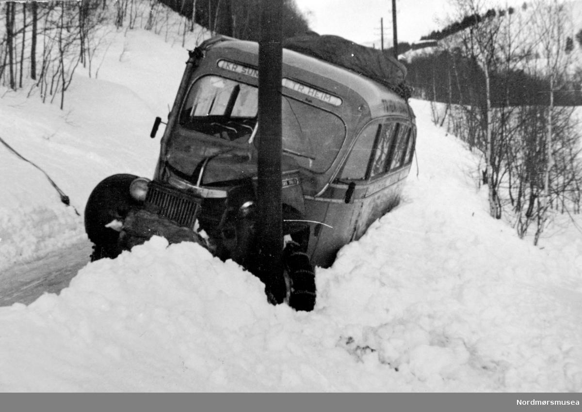 Trafikkulykke, hvor vi ser rutebussen mellom Kristiansund - Trondheim har kjørt av veien en vinterdag. Bildet er datert 1943. Det er usikkert hvor den kjørte av veien. Se også KMb-1986-017.0188. Fra Nordmøre museums fotosamlinger.
