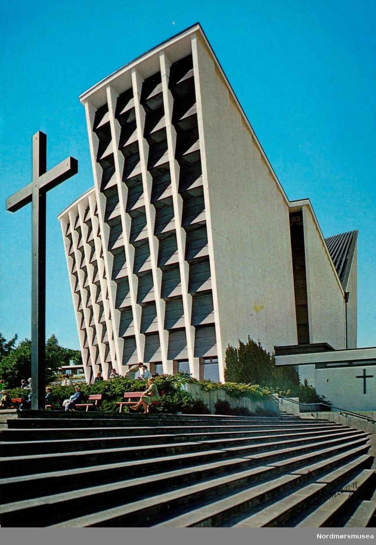 """Postkort """";T-B-17""""; med motiv fra den nye Kirkelandet kirke i Roligheten.    Etter krigen i 1945 tok kommunen opp spørsmålet om gjenreisning av kirken. Spørsmålet som ble reist først var plassering av kirken, og 2. november ble dette forelagt menigheten. Dette skulle vise seg at å bli vanskeligere enn antatt. Flere forslag ble presentert, som Barmannhaugen og gamle fengselstomta, men ingen av disse forslagene ble godt mottatt i menighetsrådet. Over de neste årene med flere diskusjonsrunder, ble det tilslutt under formannskapets møte den 29. oktober 1955 vedtatt å anbefale at kirken plasseres i Roligheten etter bygningssjefens utarbeidede alternativ 2-55.  Problemet lå nå i at kommunen ikke var eier av Roligheten. Også dette første til forsinkelser da kjøpet havnet i rettssystemet, og ble ikke løst før 26. september 1957 da høyesterett nektet å ta saken inn til behandling. Likevel, arbeidet med reguleringsplanen pågikk hele tiden, og denne ble vedtatt av bystyret den 2. juni 1956, stadfestet 1. august samme år, og fulgt opp ved Kgl. res. av 18. oktober 1957.   Formannskapet hadde da gitt eierne tilbud om å kjøpe tomten, og med Kristiansund skjønnskommisjon som fastsetter av voldgiftsrett-prisen, ble tomtekjøpet gjennomført. Første gang i 28. oktober 1958 da kommunen kjøpte 5500 m2 eiendom til kr. 99.000, og andre gang med kjøp av tilleggsjord 15. desember 1961 til en verdi av kr. 51.000. Totalt kr. 150.000.  Allerede da var en plankomite blitt satt ned for å se på planløsningen av den fremtidige kirken. Plankomiteen møttes 4. juli 1956, og forslaget ble deretter lagt frem for formannskapet den 20. september 1956. Følgende romprogram ble godkjent og stemt gjennom: forhall, kor, Sal med 600 sitteplasser, menighetssal til 100-150 personer som kan knyttes sammen med hovedsalen, dåpsrom, sakristi, organist og notearkiv, velferdsrom, kjøkken til menighetssal, orgelgalleri, rom for orgelmaskin, materialrom, samt eventuelt kontorer som et alternativ under anbudskonkuransen. """