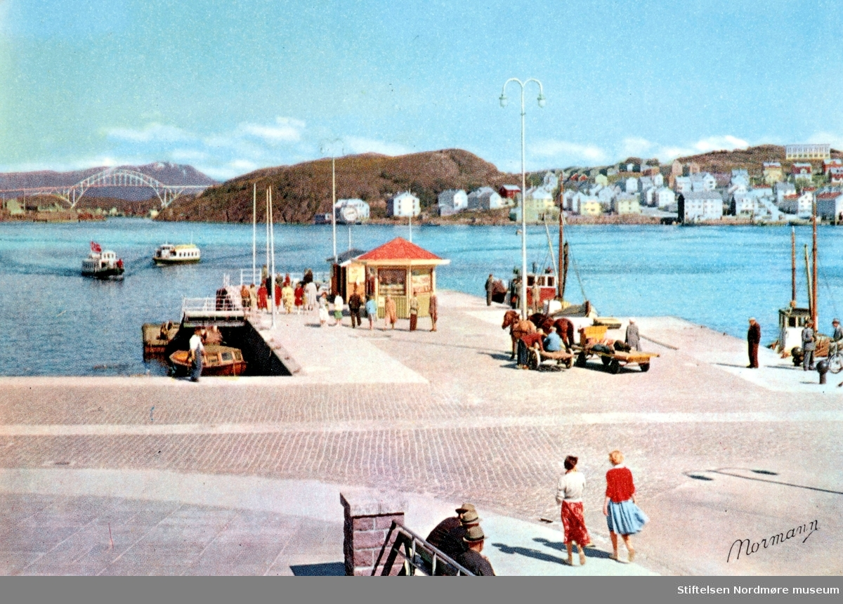 Sundbåtene Lyn og Kvikk. Sistnevnte ble solgt i 1965 (bygd i 1951). (Info: Tor Arne Skålvik 2017)  Postkort med motiv fra Piren; Kirkelandet allmenning på Kirkelandet i Kristiansund, mens det ennå var en Narvesenkiosk på Piren (og før Bergsli sin kiosk der). I bakgrunnen ser vi Nordlandet til høyre, samt Nordsundbrua som knytter Nordlandet sammen med Gomalandet til venstre. Utgiver av kortet er Normanns Kunstforlag as. Datering er år 1960 til 1965. Fra Ida M. Knudtzons fotosamlinger, nå en del av Nordmøre Museums fotosamlinger.