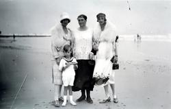 Foto av en gruppe kvinner og en gutt på stranden, ukjent hvo