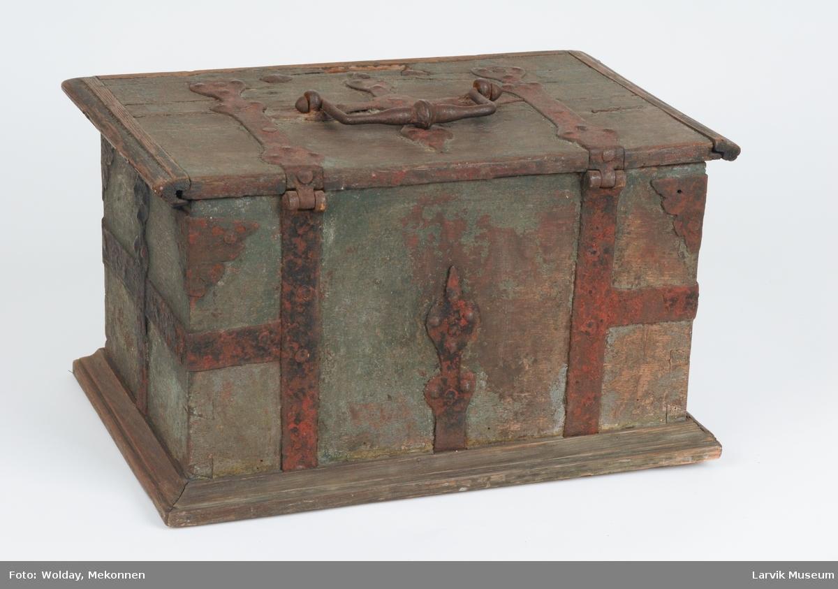 Form: flatt lokk, rette, sinkede vegger. prof.list langs lokkets kant og bunn. jernbeslag på sider og lokk. jernhåndtak på lokket.