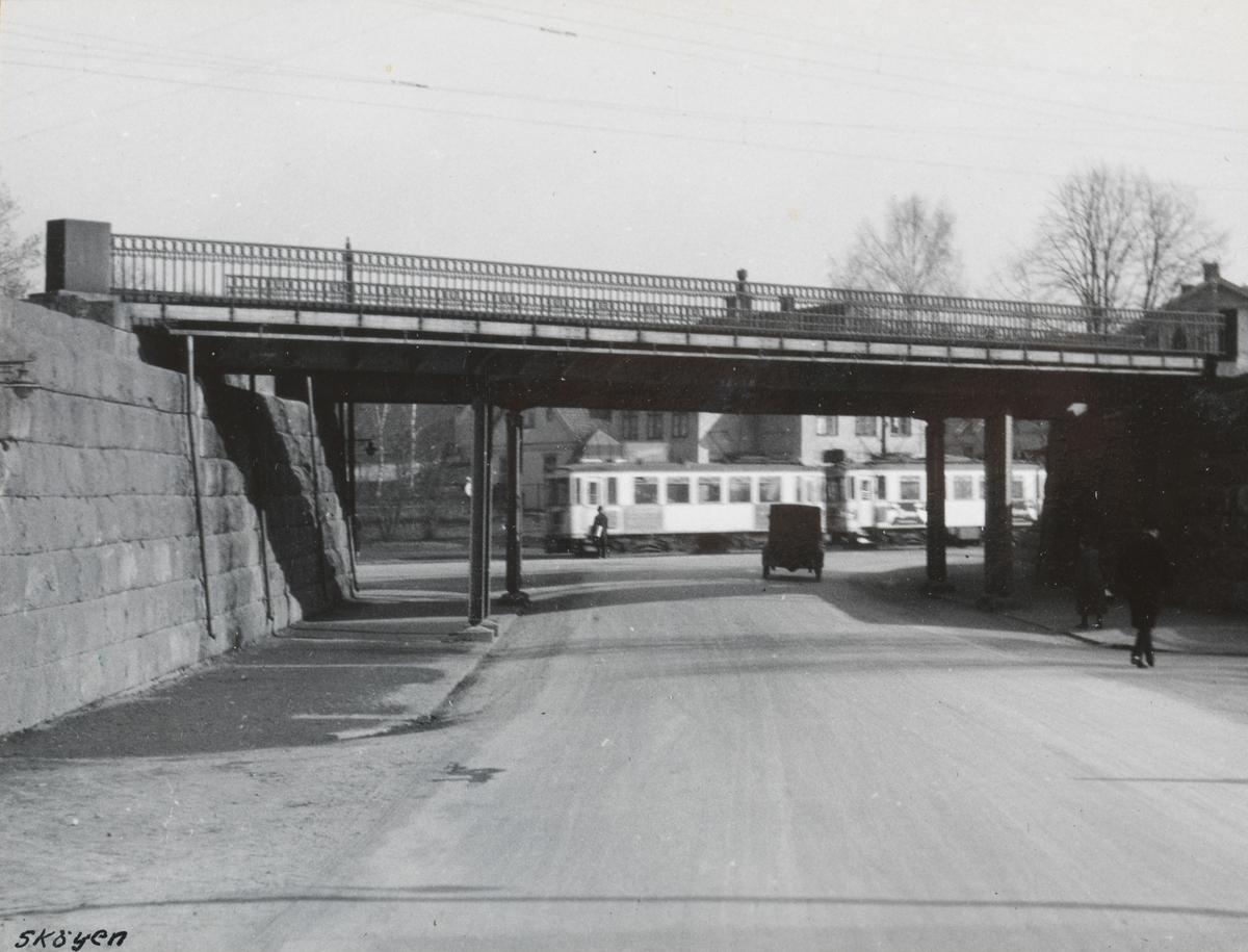 "Drammenbanen ved Skøyen. Billedtekst: ""Undergangen ved Skøyen."" I bakgrunnen sees et Bærumsbane-tog med A1-vogner fra 1924."
