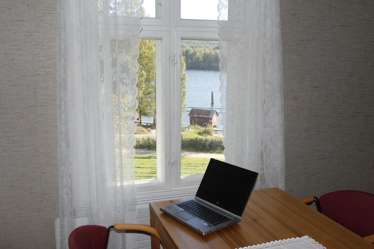 En bærbar pc står på et konferansebord ved et vindu med utsikt ut mot elva