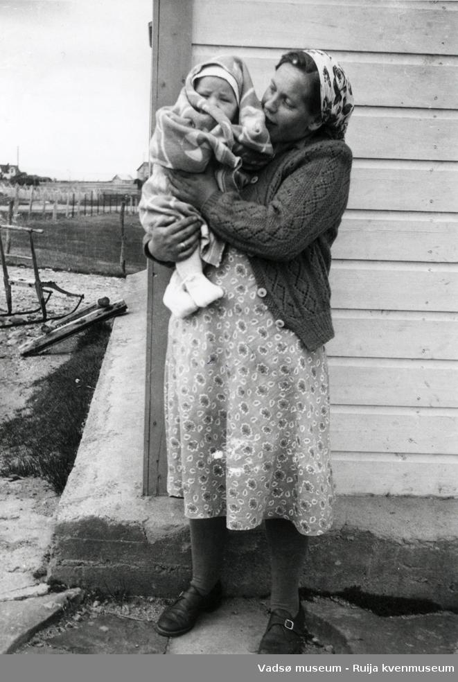 """Jenny Kærnæ med sønnen Kjell Kærnæ på armen. Utenfor barndomshjemmet til Kjell Kærnæ på """"Myhre"""" i Vestre Jakobselv."""
