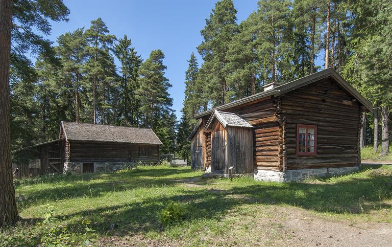 Husmannsplass med brunlig hus i halvannen etasje og med tilbygd vindfang, og en gråbgun tømmerlåve med utedo ved siden av.
