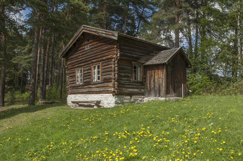 Gråbrunt tømmerhus, halvannen etasje, med tilbygd vindfang på langveggen. Huset er ei husmannsstue og ligger litt oppi en bakke med gress og løvetann.