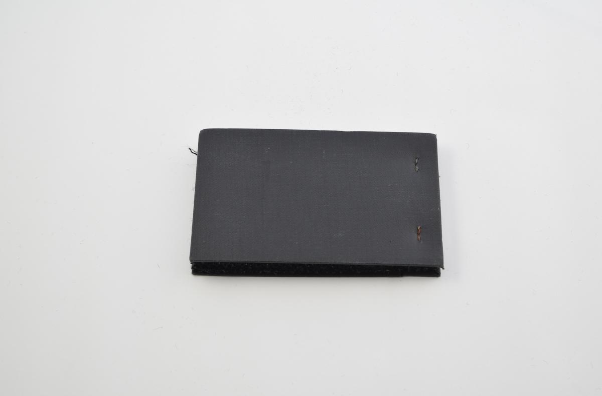 Prøvebok med 9 prøver. Middels tykke ullstoff uten utpregede mønster. Alle mørke fargetoner. Alle stoffer er merket med en rund papirlapp  festet til stoffet med stifter, hvor nummer er påskrevet for hånd.   Stoff nr. 175 (grå), 180 (grå), 183 (mørk grønn med røde ruter), 209 (mørk blå-grå), 280 (sort med hvit), 295 (mørk grå), 298 (sort med hvit), 310 Blå-grå, 320 (sort med hvit).