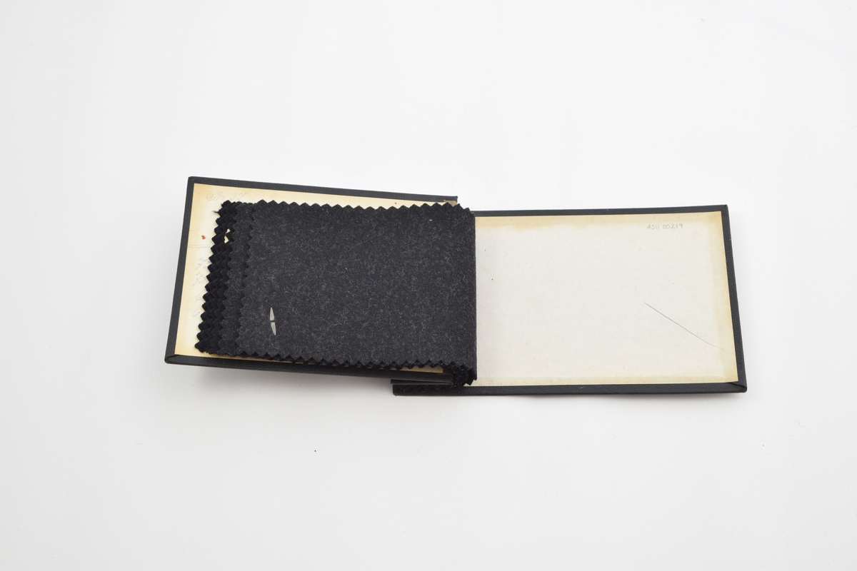 Prøvebok med 6 prøver. Tynne ullstoff uten utpreget mønster. Alle stoffer er merket med en rund papirlapp festet med melallstifter hvor nummer er påskrevet for hånd. Stoffene er i mørke fargetoner, fra mørk grå til sort.   Stoff nr. 727 (sort), 728 (sort), 734 (sort), 735 (sort), 660 (grå), 661 (grå).