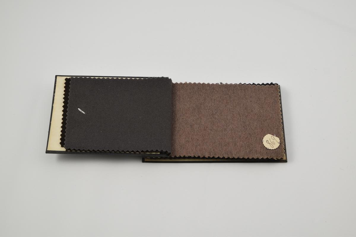 Prøvebok med 8 prøver. Middels tykke til tykke ensfargede stoffer i grå og brune fargetoner. Alle stoffer er merket med en rund papirlapp festet med metallstifter hvor nummer er påskrevet for hånd.  Stoff nr. 867 (brun), 868 (grå), 869 (brun), 870 (grå), 871 (sort), 872 (grå), 873 (brun). 874 (grå).