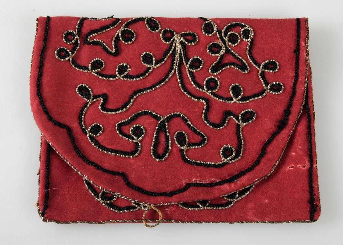 Väska av rött kläde med applicerade svarta silkessnoddar och guldsnoddar. Fodrad med vitt siden.