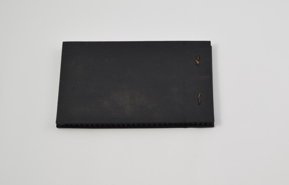 Prøvebok med 5 prøver. Tynne ullstoff med diskret ruter og striper. Alle stoffer er merket med en rund papirlapp festet med metallstifter hvor nummer er påskrevet for hånd.  Stoff nr. 1071 (fiolett med striper), 1200/15 (grå med ruter), 1324 (fiolett med striper), 1327 (fiolett med striper), 1330 (fiolett med ruter).