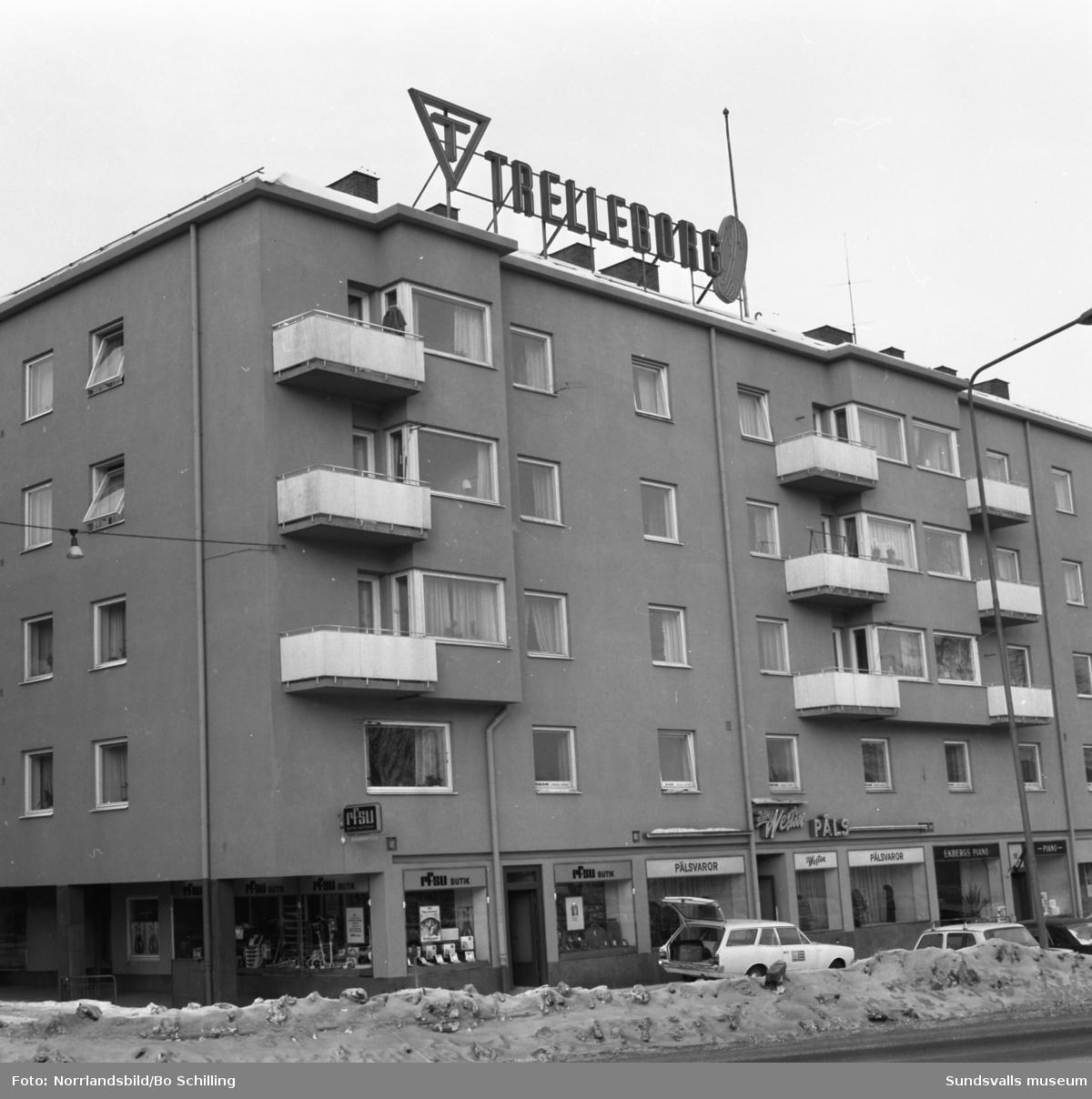 Exteriörbild av fastigheten vid Strandgatan 12-14. På taket en stor skylt med Trelleborgs Gummi AB. I gatuplan butikerna RFSU, Alf Westin Päls och Ekbergs piano.