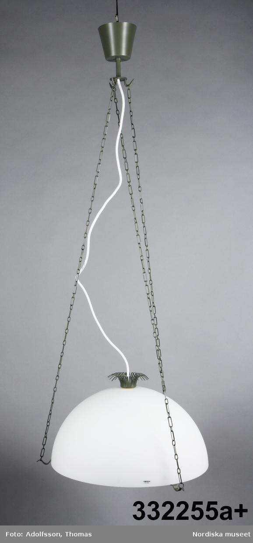 Taklampa för elektrisk belysning. Halvsfärisk lampskärm i vitt opalglas med öppningen nedåt vilande på metallring.  Tre nedåtböjda krokar placerade på ett jämnt avstånd ifrån varandra runt ringen. Från krokarna löper tre metallkedjor som möts i i lätt konad upphängningsdel/takkopp. Mitt uppe på skärmen  en liten plymdekoration av metall. Metalldelarna handgjorda och lackerade i antikgrönt. Inuti skärmen lampsockel E 27 (tjock sockel) för lampa med max 75 Watt. Rekommenderad lampa: lågenergi 660 Lumen/11 Watts effekt. Vit sladd från skärmens mitt avslutas med kontakt.  /Maria Maxén 2015-12-14