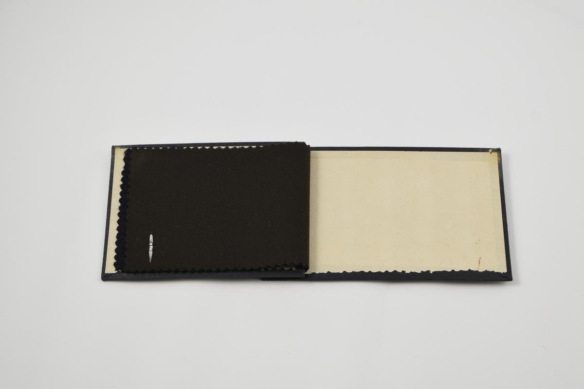 Prøvebok med 3 prøver. Tynne ensfargede stoff, to av dem med fiskebenvevmønster, alle i mørke fargetoner.  Alle stoffer er merket med en rund papirlapp festet med metallstifter hvor nummer er påskrevet for hånd.   Stoff nr. 1000/   (sort - kyperbinding?), 1000/1 (sort - fiskebenvevmønster), 1000/2 (brun - fiskebenvevmønster).
