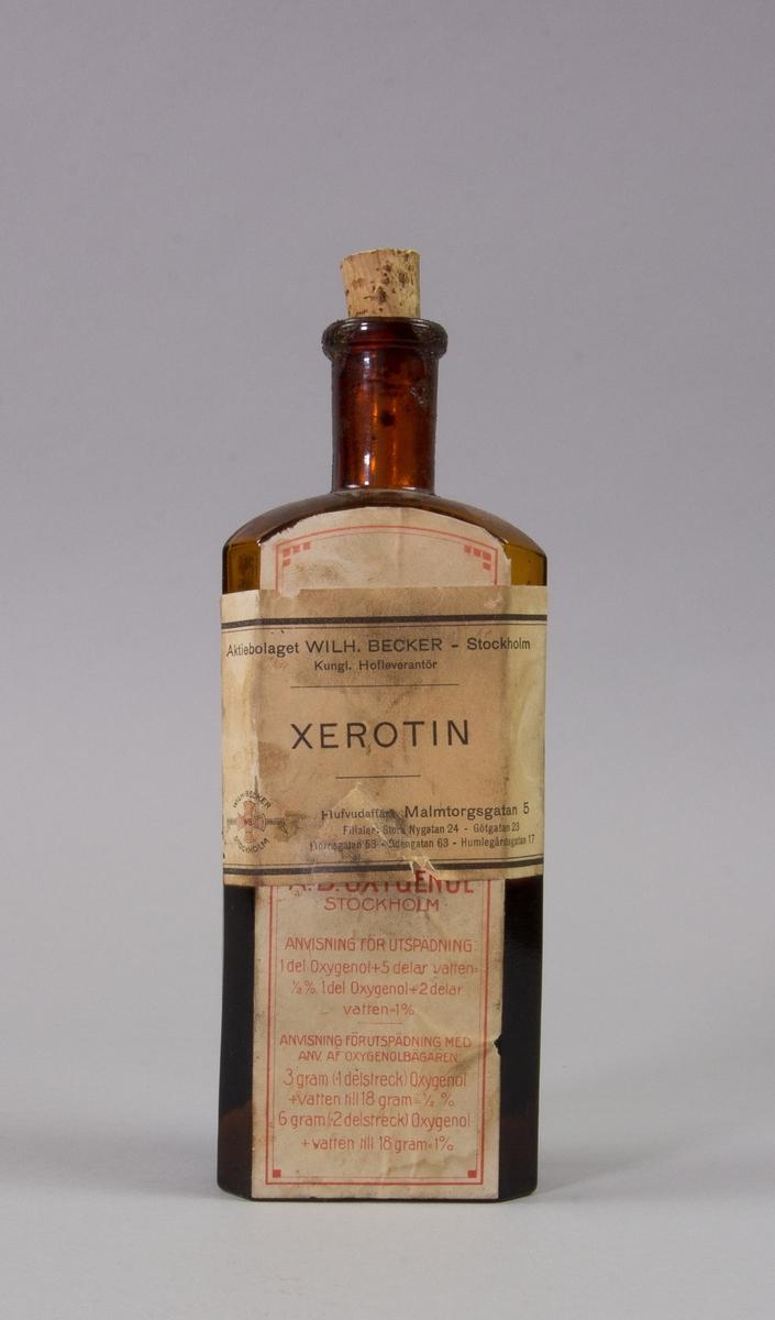 Flaska av brunt glas, rektangulär med kork för xerotin. Har ursprungligen innehållit oxygenol. Fylld tll hälften med xerotin.