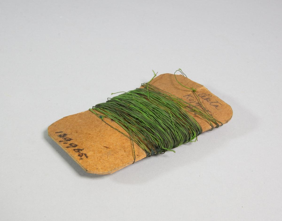 Koppartråd, tunn, upplindad i ett stort antal varv på pappbit. Ärjad, grönaktig.