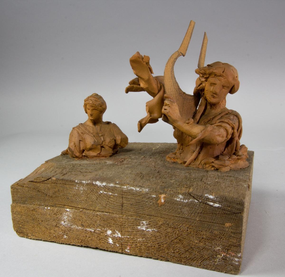 Två kvinnofigurer, midjebild. En spelar på en lyra.