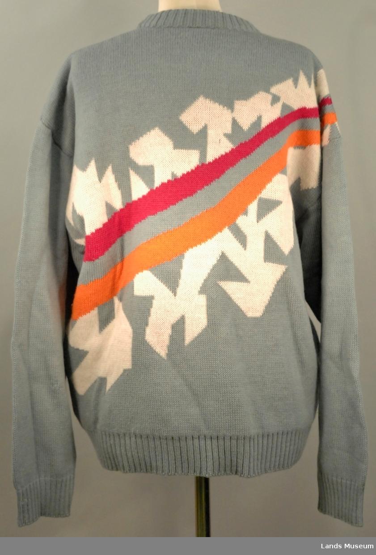 Grå genser i ull med mønster på skrått over frå høgre skulder ned mot venstre; Fakkelmannen søm løper brodert på genseren, brodert i svart. Stor pin med OL Lillehammer 1994-logo på venstre side av genseren.