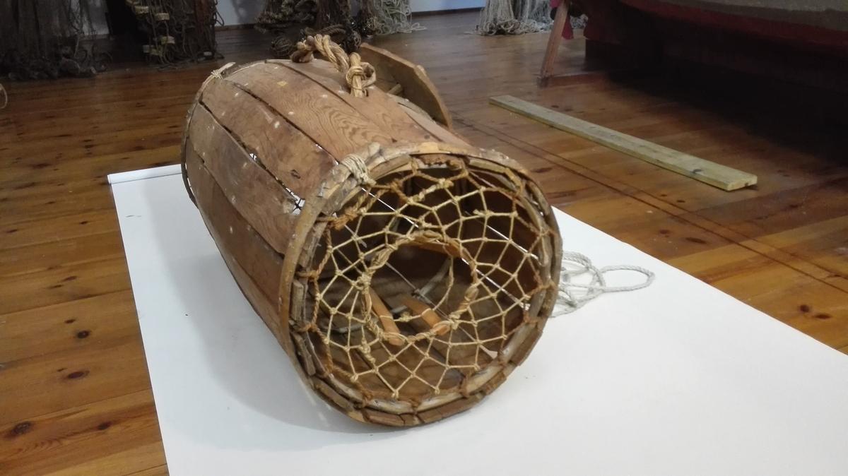 1 hummerteine.  Hummerteine av gammel type fra Söndhordland. Laget av töndestaver og i furu av en tönde med aolbinding og tragt for begge ender. Hummerteinen blev utsat, hvor man kunde se bunden og helst i en ur, ikke i aalegras. Som agn bruktes fersk fisk.  Kjöpt av Udna Sandnæs, Eidsvaag pr. Valevaag.