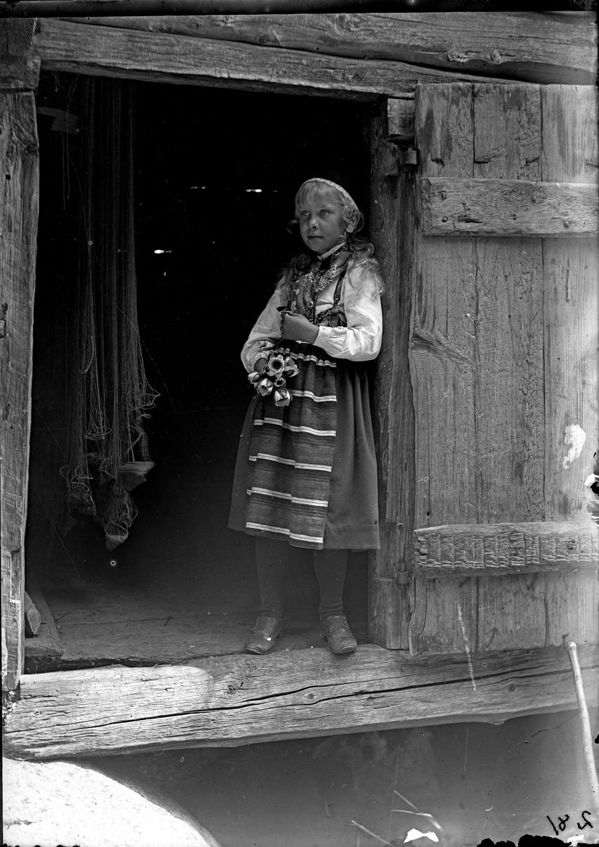 Flicka i dörröppningen till nätboden Afhulta. Fotograf okänd.
