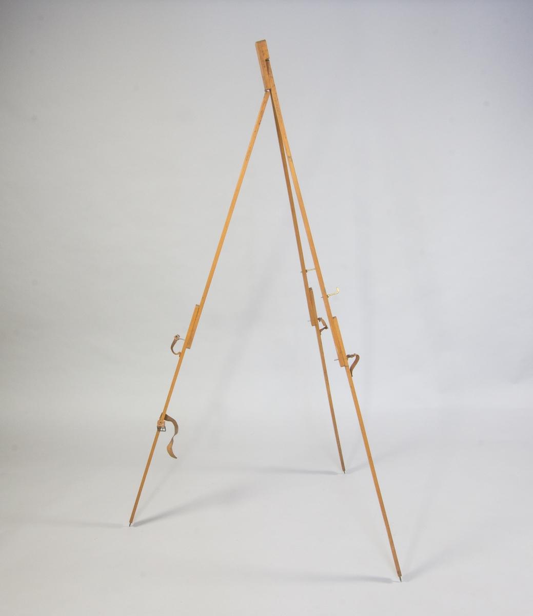 Staffli av trä, trebent. Varje ben avslutas med metallpigg. Hopfällbart.Två mässingskrokar ger stöd åt duken. En läderem med metalltapp på varje ben för att hålla ihop över- och underdel vid uppfällt läge. I hopfällt läge hålls staffliet samman med fast läderrem.