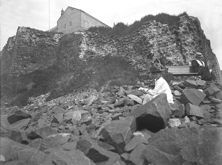 Foto av tre kvinnor som slagit sig ner framför fästningsmurarna till  Varbergs fästning. En yngre 6b37670ffb84b