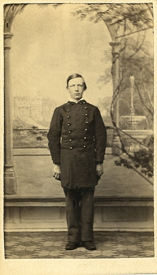Porträtt (helfigur, en face) av en tonårspojke, klädd i något slags skoluniform, mot en kulissbakgrund med en fontän m.m.Gustaf Magnus Lundgren (1851-1890), son till handl. Carl Johan Lundgren (1819-1892) och h.h. Eva Andrietta, f. Björklund, Växjö.