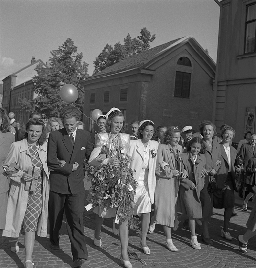 """Studenterna, andra dagen, 1947.Studenter och anhöriga på väg uppför Storgatan mot Stortorget.I bakgrunden skymtar bl a Strykjärnet. Angående avgångsklasserna 1947 - Se """"Lärare och Studenter vid VäxjöHögre Allmänna Läroverk 1850-1950"""" (1951), s. 183-187, 286."""
