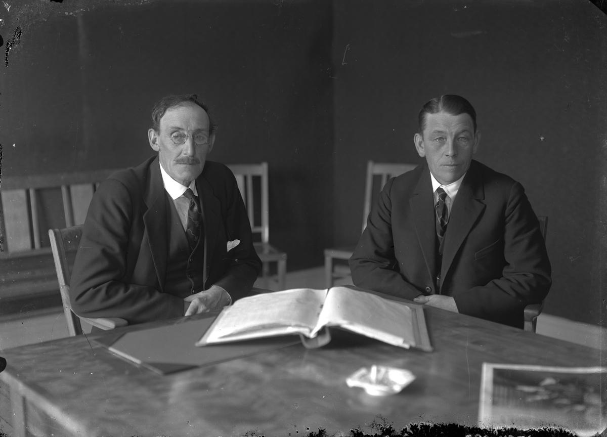 Två män vid skrivbord.