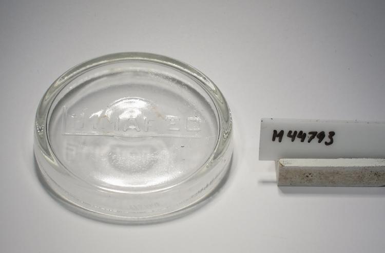 """Lock till konserveringsburk. Cylindriskt. Ofärgat klarglas. Märkt på locket. Se """"Signering, märkning"""" ovan. Inskrivet i huvudkatalogen tidigast 1990. Funktion: Lock till konserveringsburk"""
