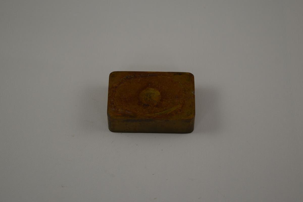 Rektangulær form til produksjon av såper  ved Saanums Sepefabrikk i Mandal. Kun overdel, mangler sannsynligvis bunn. Sannsynligvis jern med messing utenpå. Beslått med plater av messing, synlige beslag. Rektangulært relieff med tekst.