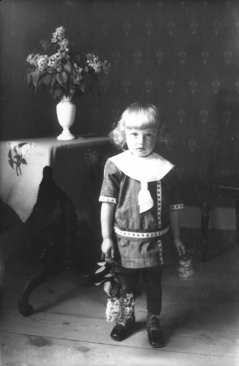 Liten flicka med syrenkvist i handen.