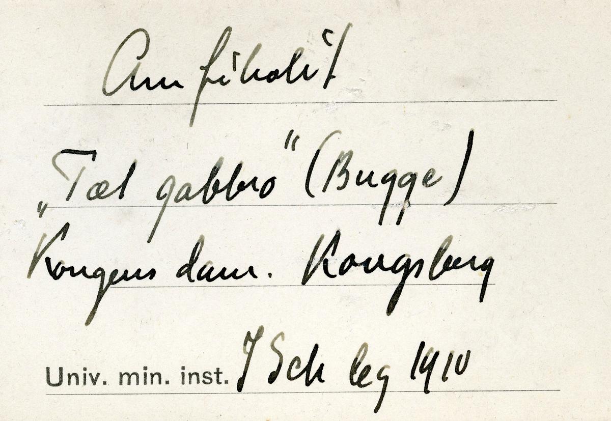 To etiketter i eske:  Etikett 1: Amfibolit «Tæt gabbro» (Bugge) Kongens dam. Kongsberg J Sch leg 1910  Etikett 2: Amfibolit «Tæt gabbro» (Bugge) Kongens dam, Kongsberg. J. Schetelig leg. 1910