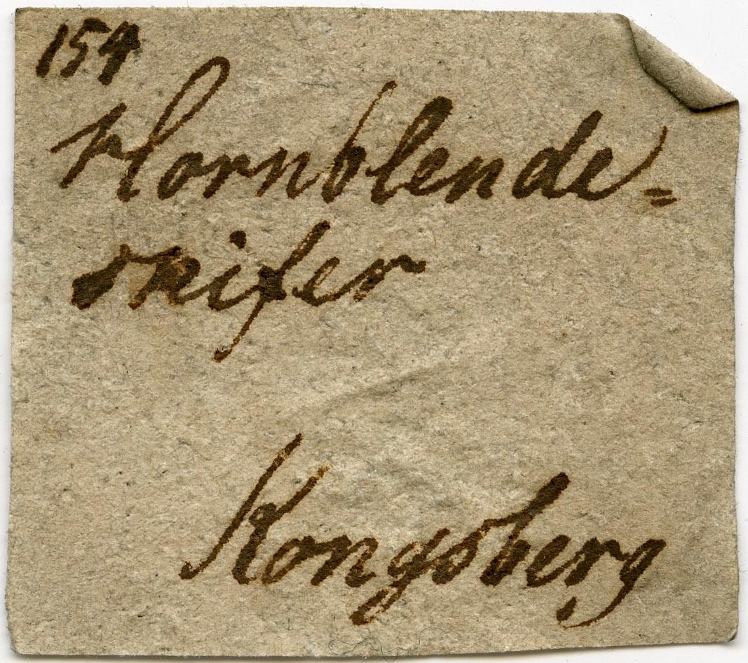 Utydelig etikett på prøve  To etiketter i eske:  Etikett 1: 154 Hornblende- skifer Kongsberg  Etikett 2: Hornblendeskifer (med Granat). Kongsberg