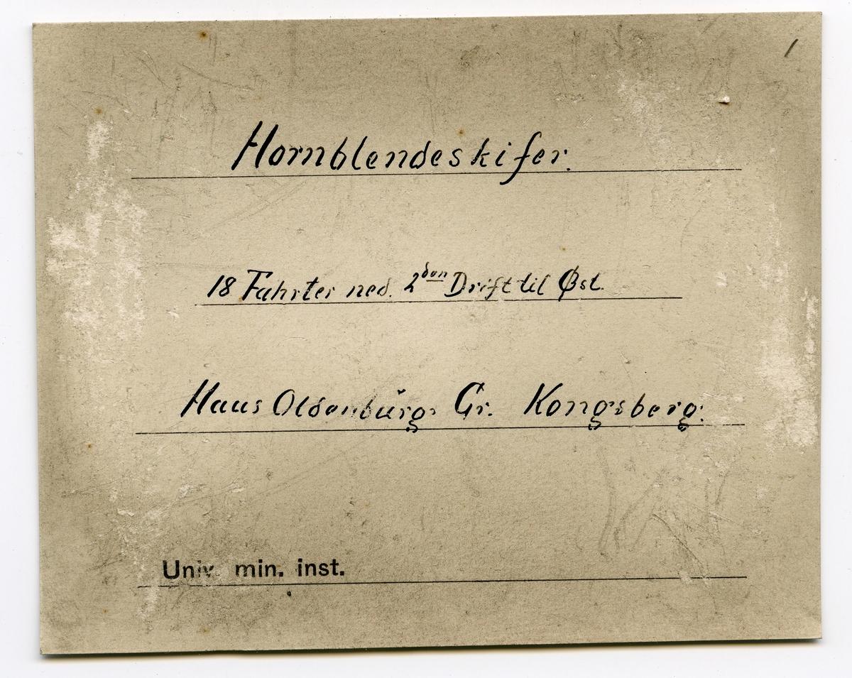 To etiketter i eske:  Etikett 1: Indlagte er fra 18 Fahrter ned. 2den drift til Øst fra Hausoldenburg Stoll.  Etikett 2: Hornblendeskifer 18 Fahrter ned 2den Drift til Øst Haus Oldenburg Gr. Kongsberg.