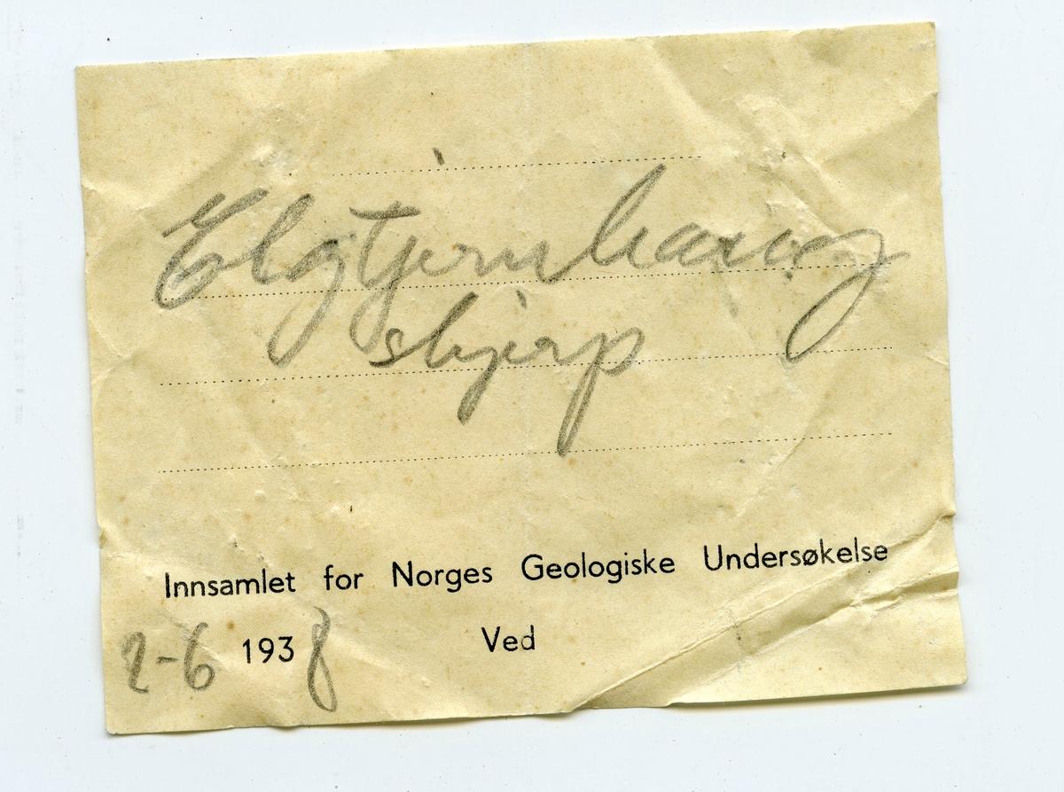 To prøver  To etiketter i eske:  Etikett 1: Elgtjernhaug skjerp 2-6-1938  Etikett 2: Elgtjernhaug skjerp Kongsberg 2-6-1938 Neumann